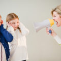 USA, Jersey City, New Jersey, mother shouting at daughters (8-11) through bullhorn